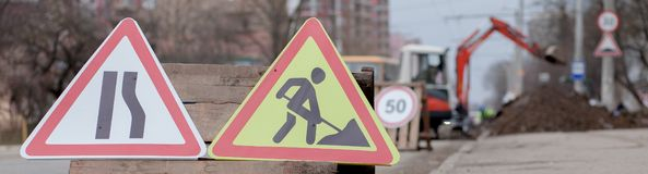 Road signs, detour, road repair on street background, truck and excavator digging hole.  stock photo