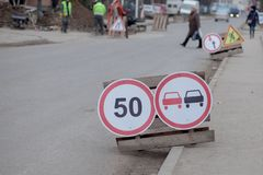 Road signs, detour, road repair on street background, truck and excavator digging hole.  stock image