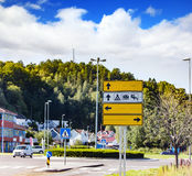 Road signs with links at roundabouts. In hilly town stock image