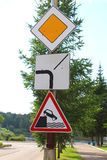 Road signs: main road, the direction of the main road, leaving the embankment Stock Photo