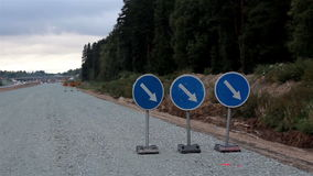 Road signs at the side of the road showing road is under construction. And no vehicle is using the road. A road is blocked with signage arrow down stock footage