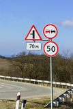 Road signs, speed limits and ban on overtaking at a sharp turn of the highway Stock Images