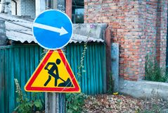 Road signs, traffic sign on the background of a green fence and a brick wall, traffic sign to the right, road works sign. Traffic rules, driving stock photo
