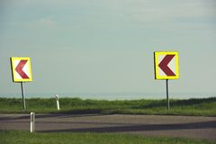 Turn left sign on a country road. Road signs warning drivers about ahead dangerous curve stock photo