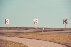 Turn left sign on a country road. Road signs warning drivers about ahead dangerous curve stock image