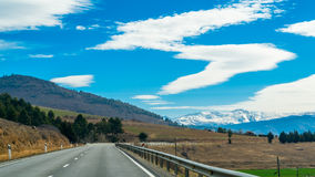 Road and sky. Road, sky with beautiful clouds and mountains Stock Photography