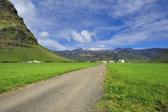 Road, sky and meadow. Road near waterfall Skogafoss, Iceland Royalty Free Stock Photos