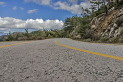Road 2 Sky. A narrow road on a mountain with a partially clouded sky above Stock Image