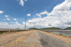 Road slope on the dam with water, mountains and clouds in beautiful blue sky at noon sun light Stock Photos