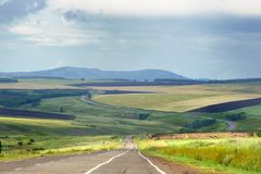 Road through smooth grass hills and steppe in Khakassia, East Siberia, Russia. royalty free stock photography