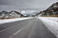 Road in the snow. Long road in the winter snow near a dam Stock Photos