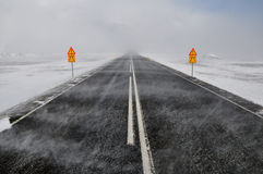 Road in a snow blizzard, Iceland. Road in a snow blizzard and two attention sings, Iceland Stock Images