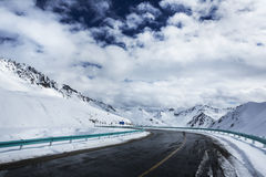 Road in the snow capped mountains Royalty Free Stock Photos