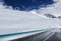 Road in the snow capped mountains Stock Image