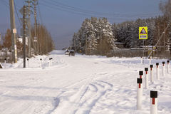 The road in the snow passing by village houses and forest Royalty Free Stock Image