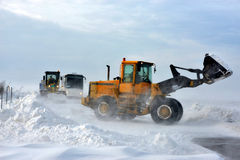 Road in snow storm. A snowplow clearing a road Royalty Free Stock Photo