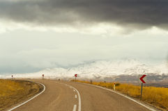Road with snowy and cloudy mountain landscape Royalty Free Stock Photography