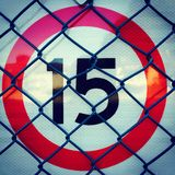 15 Road speed sign with red circle and chain link fence Royalty Free Stock Photography