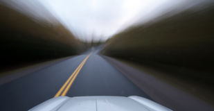 Speeding car. Speedy drive down a country road Royalty Free Stock Photos