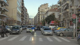At road stand christmas tree and a parked car, then through the intersection crossing road pedestrians and cars are. THESSALONIKI, GREECE - JANUARY 22, 2016: At stock video
