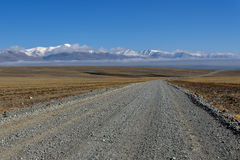 Road steppe mountain snow clouds Stock Photos
