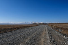 Road steppe mountain snow sky Royalty Free Stock Images
