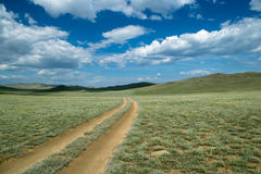 Road through the steppe near Baikal lake. The road in Tazheranskaya steppe, Lake Baikal, Russia stock image