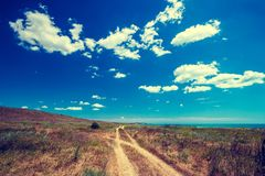 Road through the steppe to the sea Stock Photos