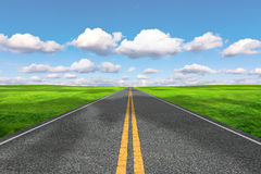 The road stretches into the distance. Against the cloudy sky Stock Photos