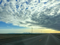 Road stretching into distance under cloudy sky Royalty Free Stock Photography