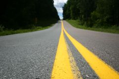 Road with stripes (DOF). Focus on extreme foreground. Road with yellow stripe; trees and sky in distance over small rise in road Royalty Free Stock Photo