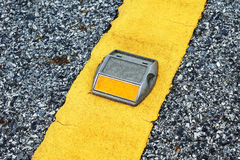 Road stud. With yellow reflector on the yellow line of asphalt road royalty free stock photography