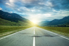 Road in summer mountains to the sunset Royalty Free Stock Photo