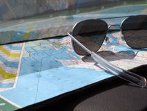 On The Road. Sunglasses and a map on the dashboard while traveling through northern Michigan Stock Image