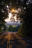 Road sunlight through trees and beautiful scenery in distance Royalty Free Stock Photography
