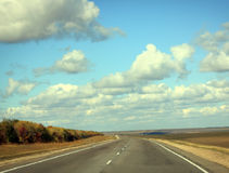 Road in sunny autumn day with cloud on the blue sky Royalty Free Stock Photos