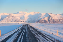 The road on a sunny day to the snow-capped mountains. Stock Image