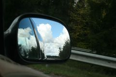 The road, sunny summer sky with clouds and trees reflection in car side mirror. As travel background royalty free stock photos