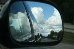 The road, sunny summer sky with clouds and trees reflection in car side mirror. As travel background stock photo
