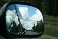 The road, sunny summer sky with clouds and trees reflection in car side mirror. As travel background stock photos