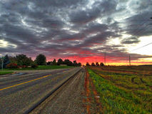 Road and sunset. Sunset road sky colors colorful red yellow brown green Stock Photos