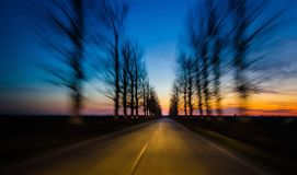 On the road. Road surrounded by two rows of trees, wich are in motion blur, implying very fast movement of a car. Effect produced by very slow shutter speed Royalty Free Stock Photos