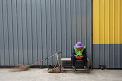 Road sweeper in Bangkok. Bangkok, Thailand - July 23, 2015: An unidentified woman road sweeper of the city of Bangkok rests after work.  Traditional broom and Stock Image