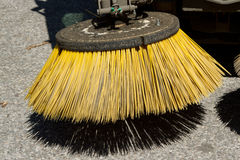 Road sweeper brush. A road sweeper brush with yellow bristles above a road and shadow Stock Image