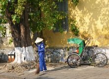 Road sweeper worker with a broom cleaning the street in Hoi An royalty free stock photos