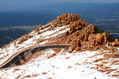 Road switchback at boulder outcrop. Overlooks valley and lake below Stock Photos