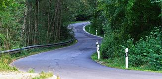 Road, tarmac, winding uphill through the woods. Road, tarmac, with side rail, winding uphill through woods summer royalty free stock photography