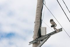 Road tax surveillance camera on concrete electrical pylon. White clouds on blue sky background stock photos