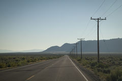 Road with Telegraph poles. Long straight road with telegraph poles in America Stock Images