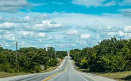 Road in Texas. Agricultural gardens. Picturesque rural highway in Texas. Journey through the southern states of the USA Stock Images